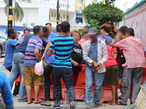 """香客在柔佛古庙门口""""派红包"""",三大种族乞讨者,争先恐后抢夺红包。"""