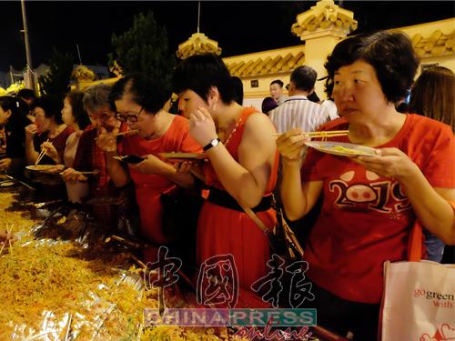 逾5000人捞生后,立即拿起纸盘和筷子当场享受美味的素鱼生。