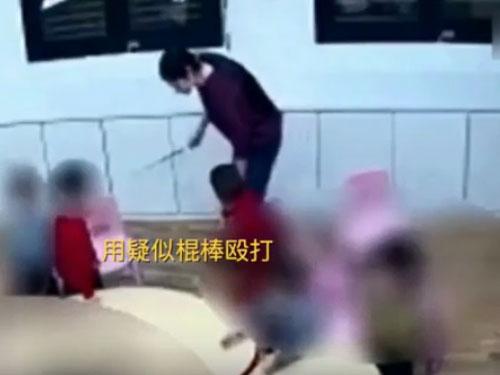 其中一名老师被拍到用教棍打幼童。(视频截图)