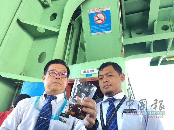 """王勇元(左)和莫哈末纳英检查船员用来装烟蒂的""""烟灰缸""""。"""