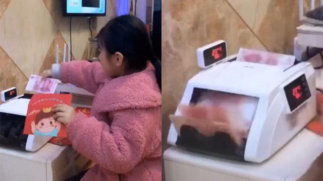 网路上流传女童用点钞机算红包钱的影片。