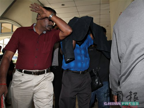 被告阿都古用被带上庭时,发现大批记者在法庭门前等候,立即脱下身上外套遮盖,避免样貌曝光。