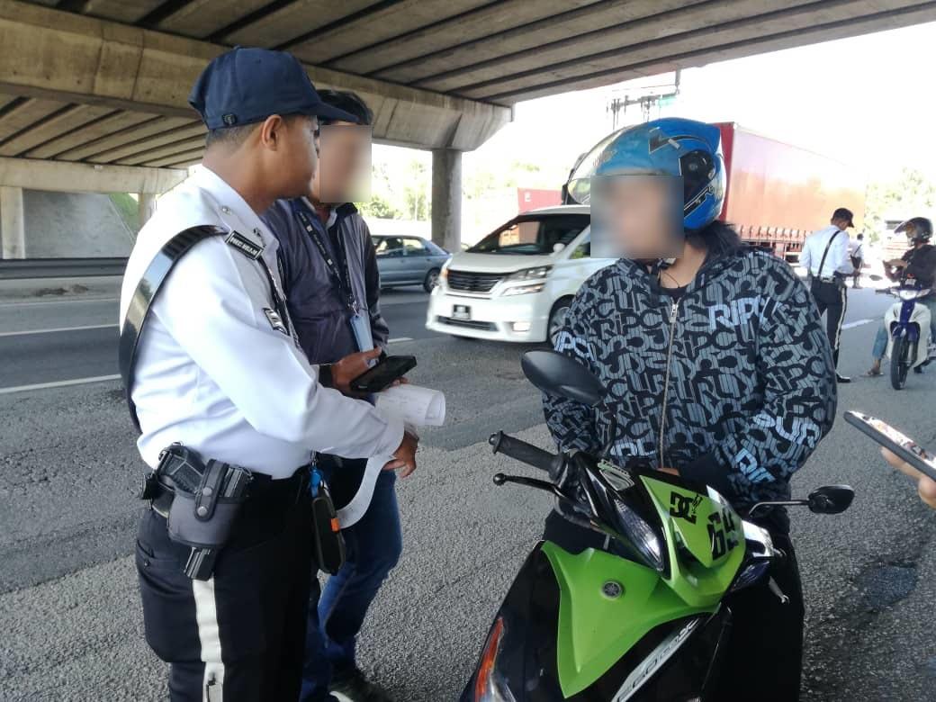 无驾照摩哆骑士落网后,因受惊不断手抖,最终花约2分钟才将身分证交给警员写罚单。