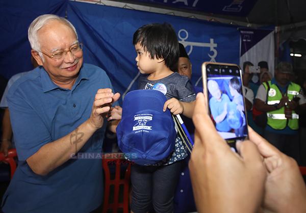 许多选民在活动上争相与纳吉自拍,纳吉也亲切与一名孩童互动。