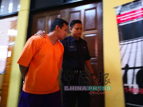 被告阿末慕拉(左)不愿面对镜头。