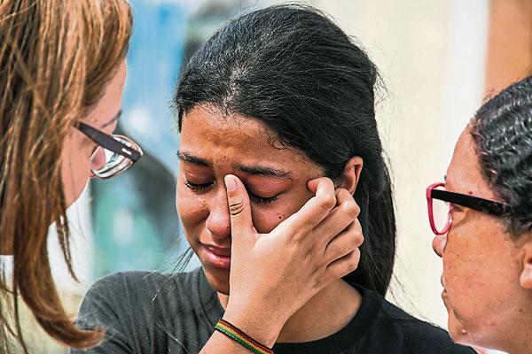 案发学校的一名女学生惊魂未定而哭泣,朋友在旁安慰她。(路透社)