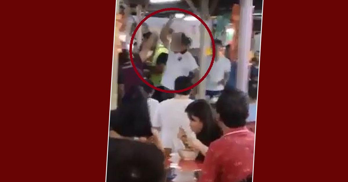 身穿白色上衣的男子疑不堪被挑衅,走回头从地上捡起一个类似盘子的物品便往老妇女方向打去。