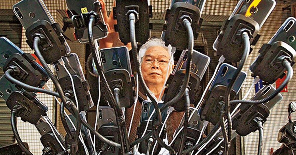 陈三元拿起他用拖把柄改装的抓宝神器,这个像糖葫芦又像孔雀开屏的手机挂架,满满挂着22支手机。