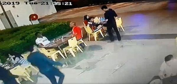 红衣男子和友人在餐馆外用餐时,突遭一群男子趋前。