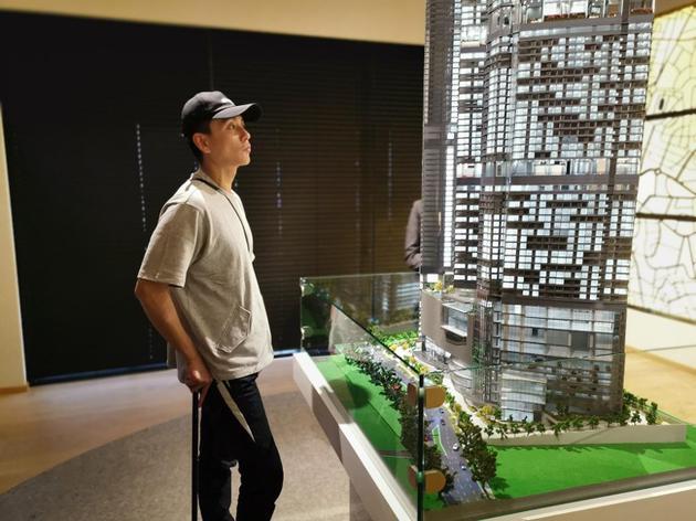 黄宗泽撑着拐杖在大马看新房楼。
