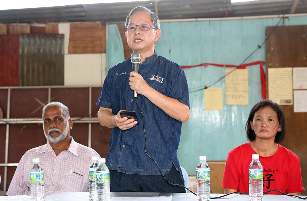 李文材(中)出席在马来甸新村拿督公庙举办的对话会。