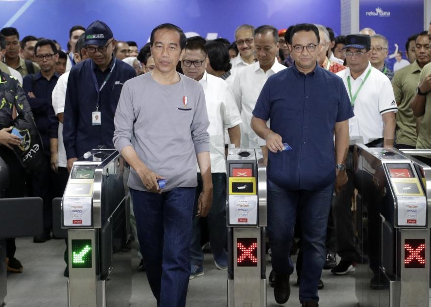 佐科威(左)经过检票处,为地铁举行开幕。