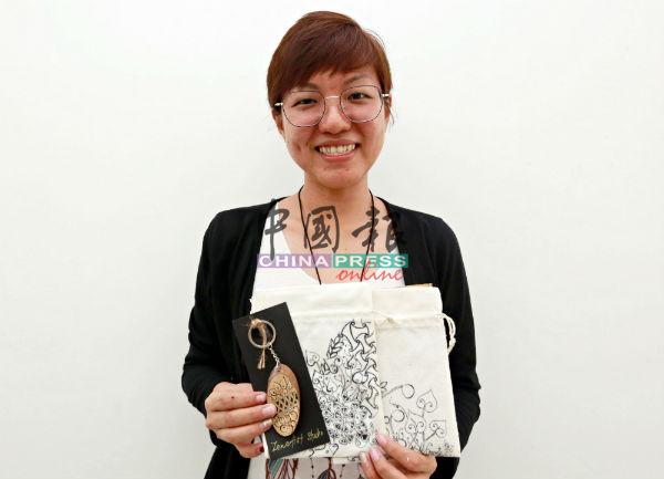 """罗翊真展示将在""""小Feel文创市集""""贩售的手工作品,商品的画全是她一笔一笔绘制上去。"""
