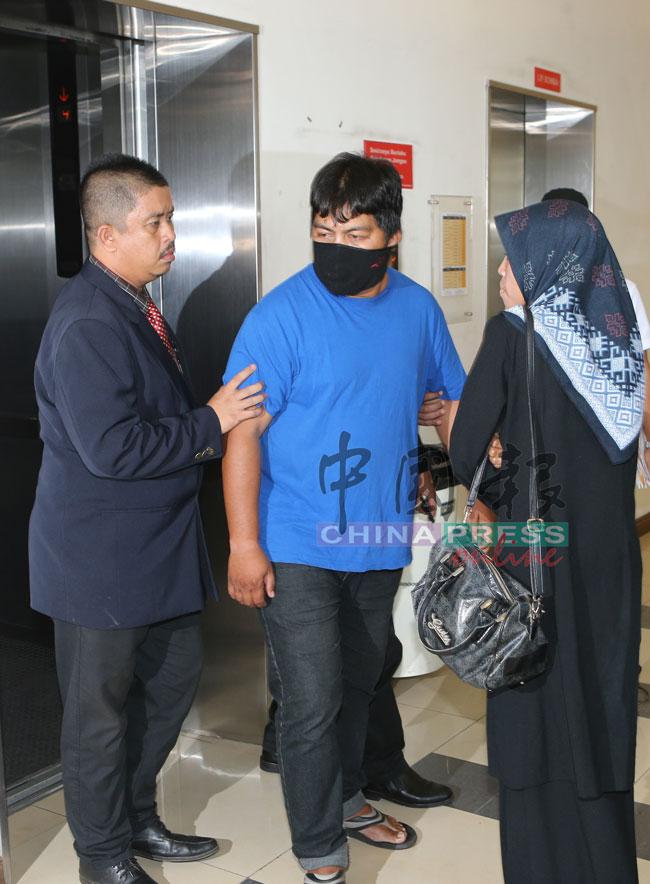 被告沙里扎(左2)在妻子(右)及反贪会官员的陪同下,出庭面控。