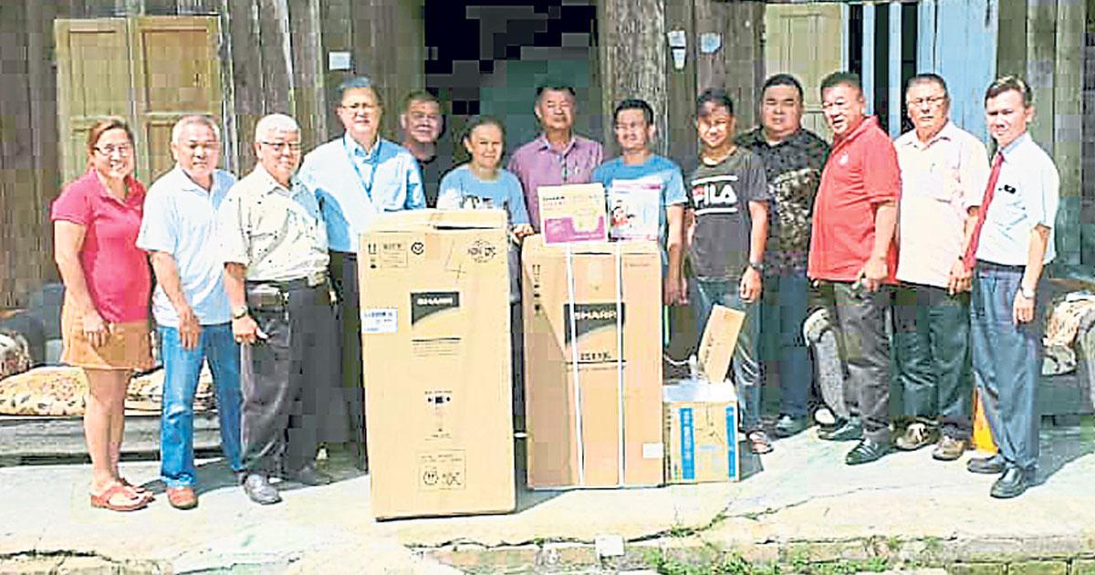 李文辉(左4)与热心人士送暖给甘孟一家八口。左7为蔡永祥;右3起为梁永康及拿督黄彦杰等。