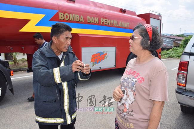 再那(左)向目击者郑凤清了解火患事件。