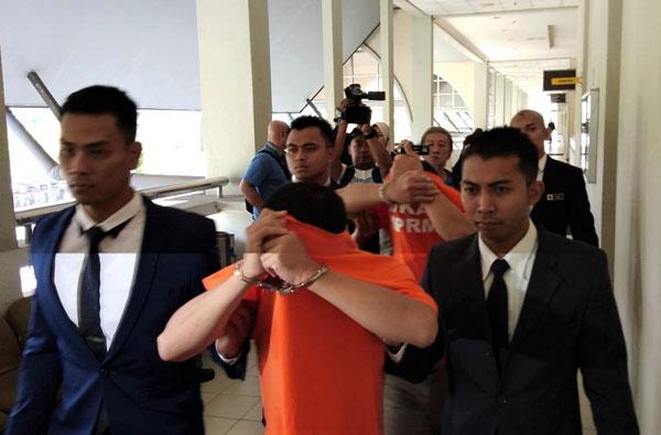 涉嫌索取贿款的两名嫌犯(橙衣者)被反贪会官员押上法庭申请延扣。