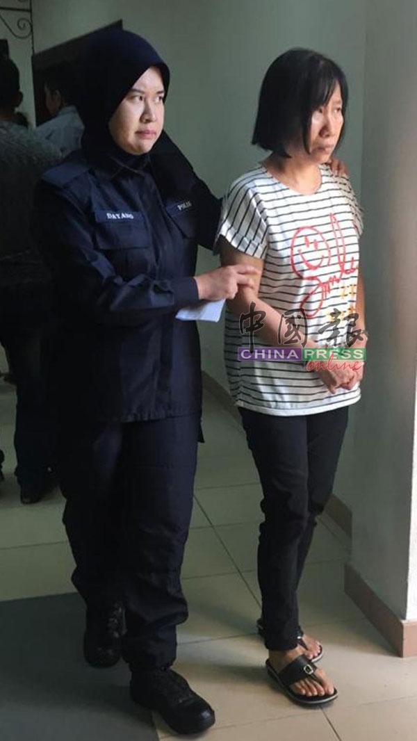 被控使用20令吉伪钞女被告双手被扣由女警押上地庭过堂。