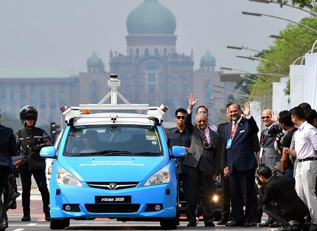 马哈迪(左2起)在哥宾星陪同下,乘坐无人驾驶汽车抵达布城机构,为大马5G科技主持推展礼。
