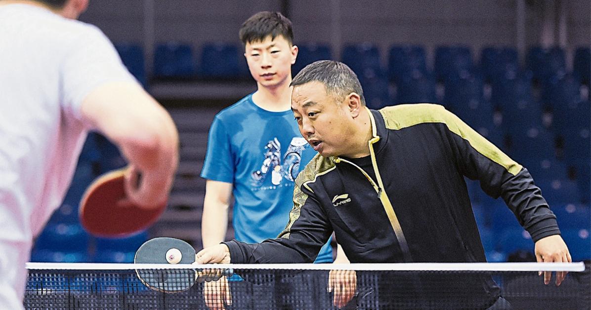 刘国梁(右)亲自下场为马龙等队员示范。世乒赛周日挥拍。(新华社)