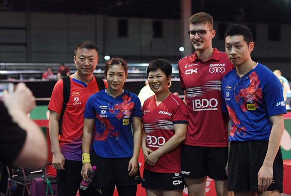 许昕(右)、刘诗雯(左2)、马拉德诺维奇(右2)、倪夏莲(中)和中国队教练马琳赛后在赛场上合影。