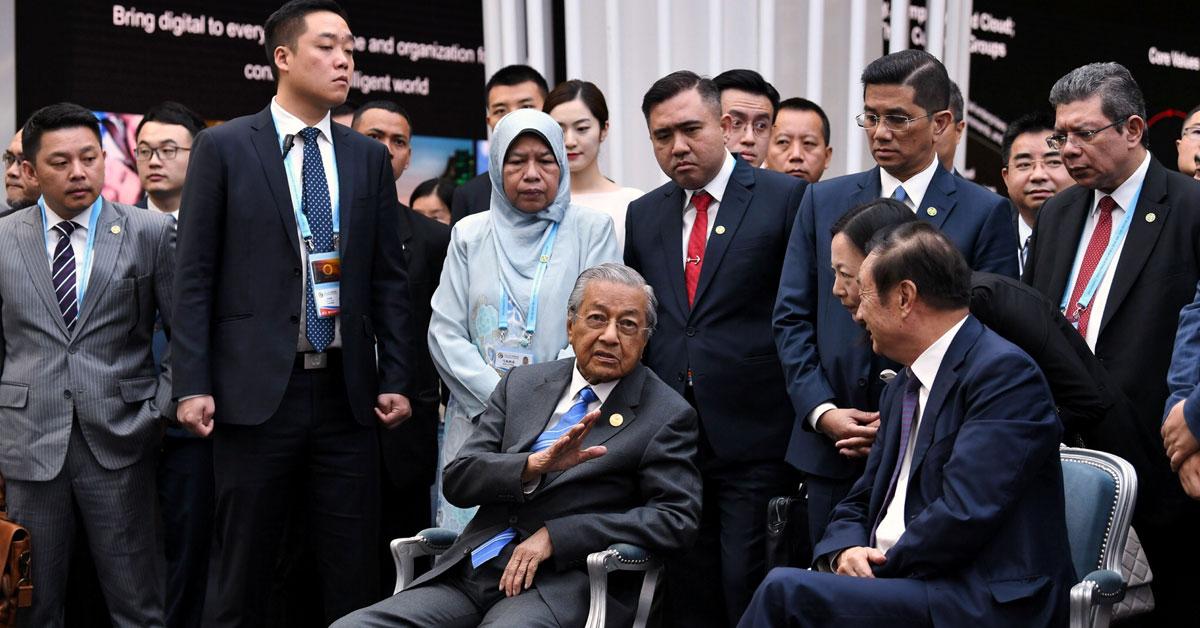 任正非(坐者右)向马哈迪讲解华为北京研究中心的业务发展。