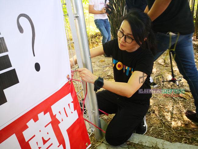 王晓庭将抗议横幅,绑在慰灵碑的栏杆上。