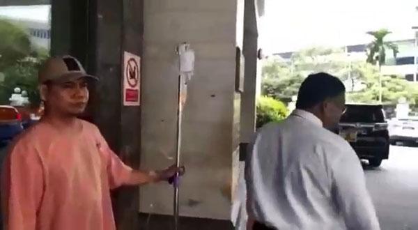 嘉马(左)吊着点滴从医院前往法庭。