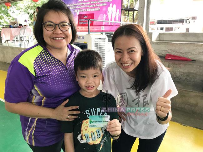 梁唯哲(中)在母亲王秀秀(左)陪同下,登记成为器官捐献志愿者,右为王丽丽竖起拇指赞好。