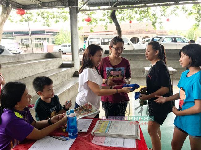 王丽丽(左)分发小手帕,给参与活动的民众。