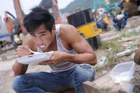 彭于晏在片场与工作人员一样蹲着吃扒饭盒。(图取自网络)