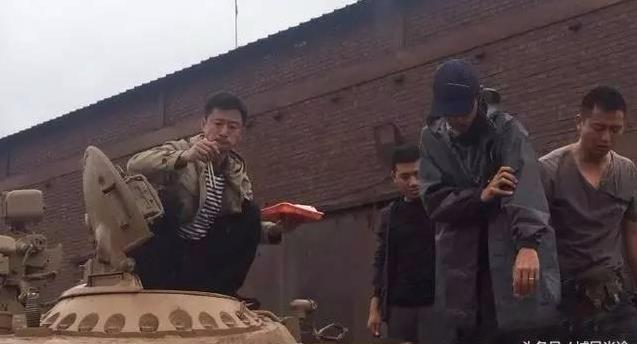 吴京霸气的蹲在坦克上吃盒饭。(图取自网络)