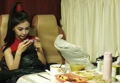 Angelababy坐在车里吹冷气,面前摆着好几个菜,还能舒适的玩手机。(图取自网络)