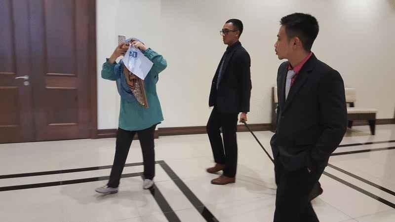 仑蒂雅(左)以纸张及水瓶遮脸避开媒体镜头。