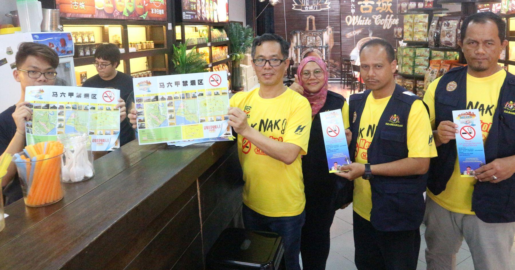 刘志良(右4)与甲卫生局官员在鸡场街派发禁烟区手册给商家们。