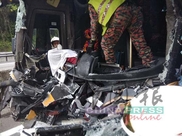 消拯员努力从残骸,移出长巴司机遗体。