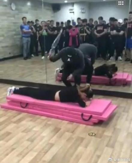 健身房员工轮流上前,伏在健身垫上接受打屁股。