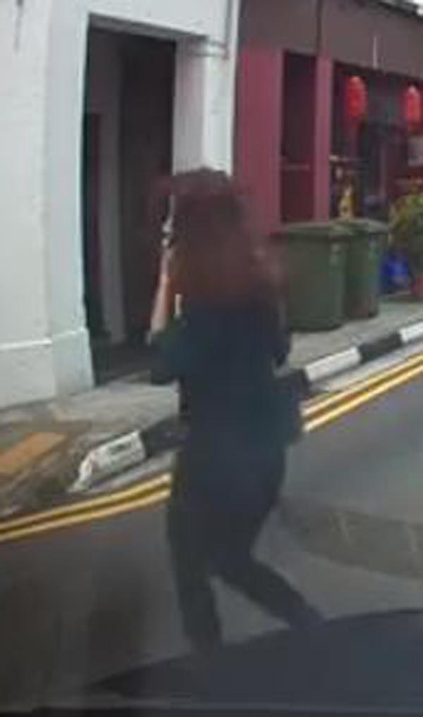 女郎橫穿馬路穿梭在車流之間,還用手機通話。(視頻截圖)