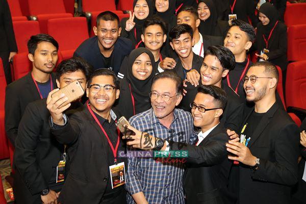 安华(前排右3)与马来西亚伊斯兰理科大学的学生一起自拍。
