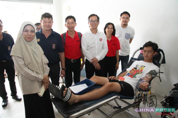 诺亚米扎(站着左起)、钟汉超、丘力鸣、刘志良、吴凤菂及梁恩来为首次捐血的邓智聪(18岁)加油打气。