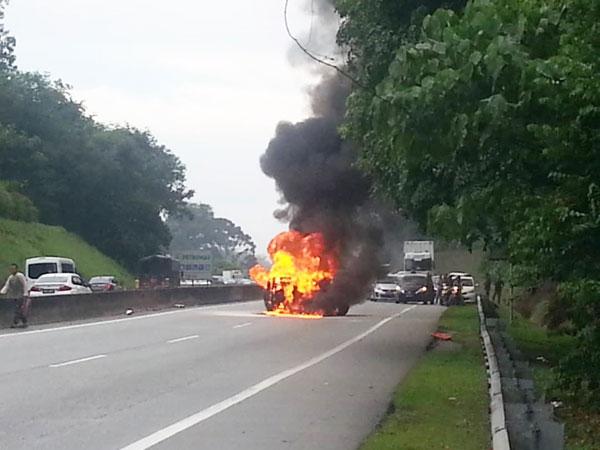 大火吞噬整辆轿车,造成交通堵塞。