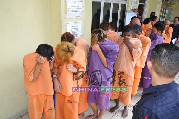 6名嫌犯被押往法庭延扣时,将上衣拉至脸部遮挡,以避免样貌曝光。