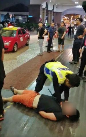 其中一名涉案者被警方压倒在地制伏,并被扣上手铐。