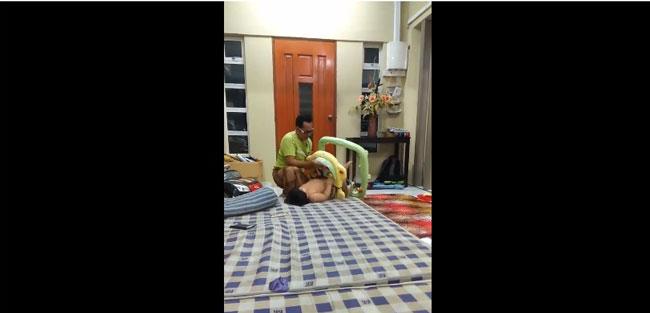父亲把学步车倒立在床上,试图从脚部把宝宝推出来。