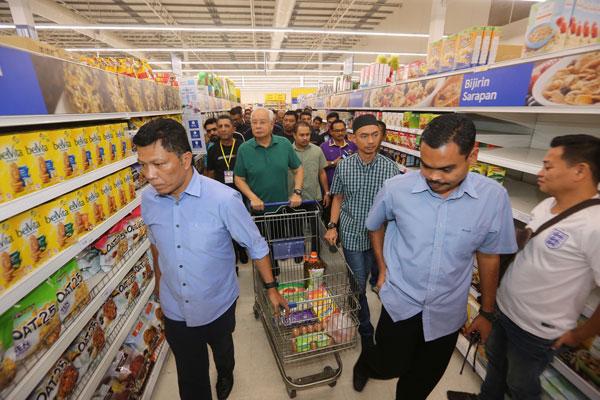身穿休闲服的纳吉(中)在保镖及支持者的陪同下,轻松购物。