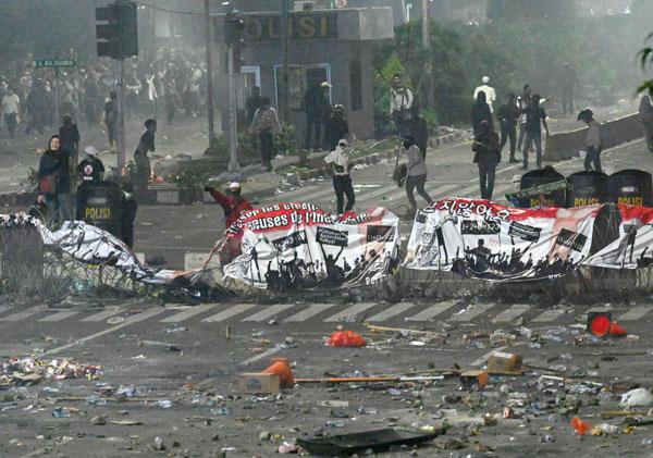 周三晚在耶加达,有示威者向军警抛物。(法新社)