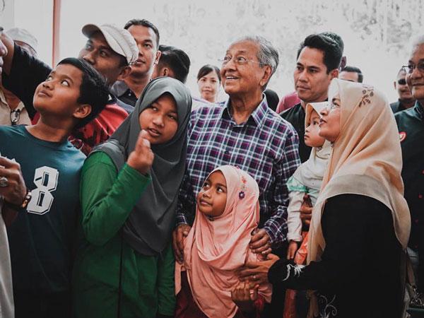 马哈迪(中)周六到卜间拉布购物,与民自拍时露出逗趣表情。