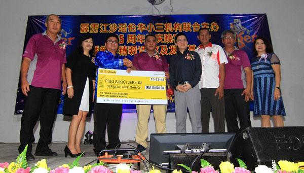 朱伟鸣(左3起)代表古拉把1万令吉发展基金模拟支票,移交给梁焕强。黄炳南(左起)、林淑宝、黄家和、黄振福、黄星光及周凤珍见证。