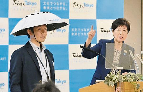 东京都知事小池百合子24日于记者会上,推出一款伞状帽子,形似斗笠,将在奥运期间发给观众使用。