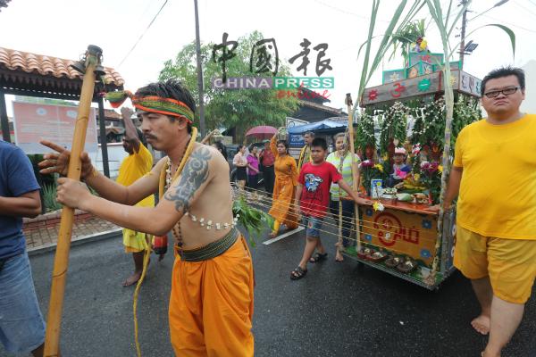 参与游行的华裔信徒,背部穿刺铁链拉着神辇游行。